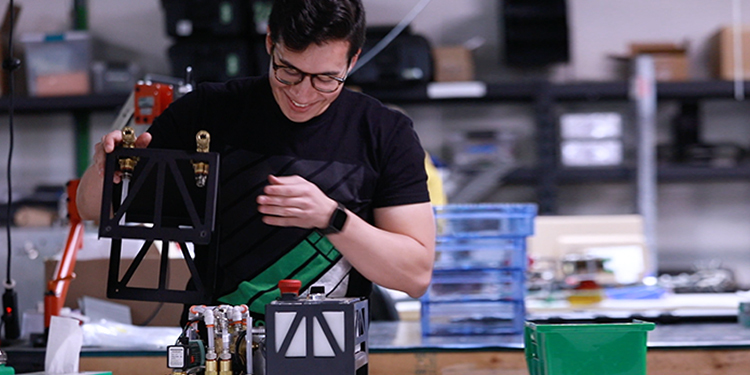 Alex Cuti working with robotic parts