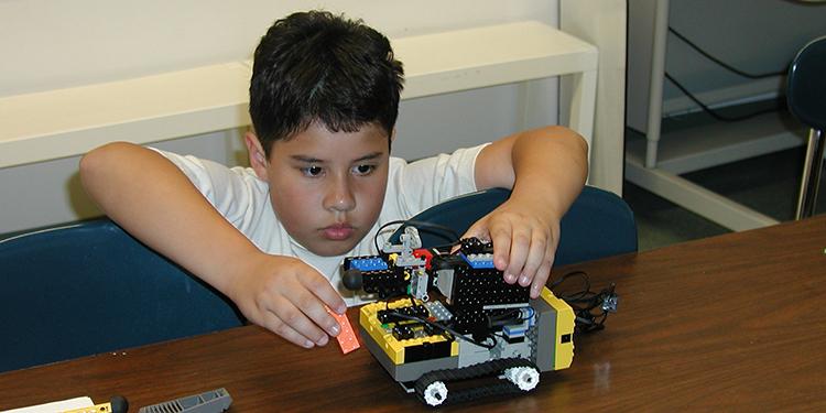 Young Alex Cuti building a Lego Mindstorm robot